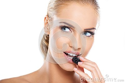 Close up of beautiful woman eating blackberries