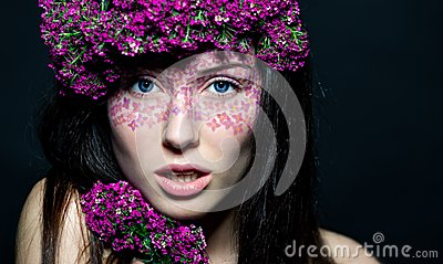 Close up of blue-eyed girl with flowers