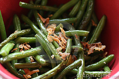 Close up bowl of cooked green beans with onion