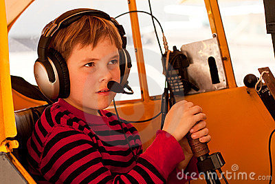 Close up of boy pretending to fly Piper Cub