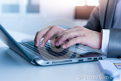 Close up of business man hands typing on laptop computer