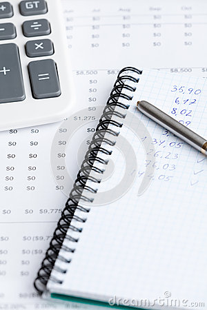 Close up of business writing pad, pen, calculator