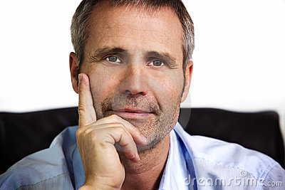 Close-up of businessman resting chin on hand.