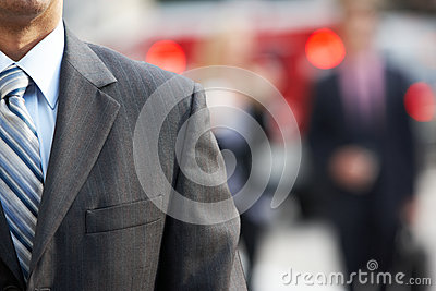 Close Up Of Businessman Walking Along City Street