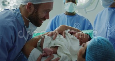 Close-up of Caucasian couple looking at their newborn baby in hospital. They are interacting with each other stock video footage