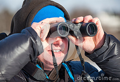 Man with binoculars looking far away