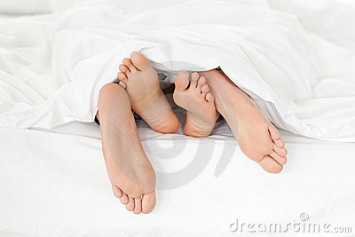 Close up of couple s feet in their bed