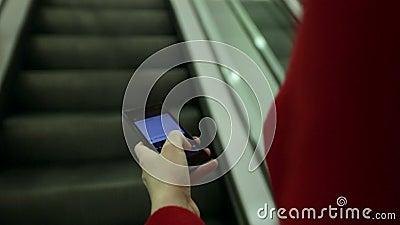 Close-up curto da mulher que datilografa em um dispositivo do smartphone ao mover sobre a escada rolante video estoque