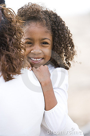 Close-up cute African-American girl in mom s arms