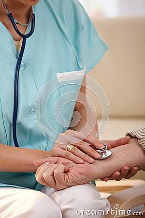 Close up da mão usando o estetoscópio no pulso