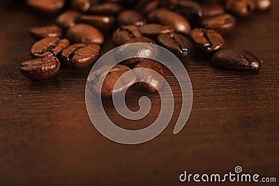 Close up de feijões de café em uma superfície de madeira escura