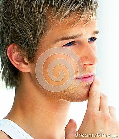 Close-up die van een knappe jonge mens is ontsproten die weg kijkt