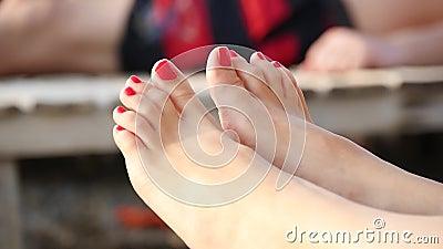 Close-up dos pés de uma mulher cujos os dedos do pé sejam pintados com laca vermelha na costa de mar filme