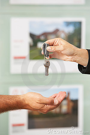 Close Up Of Estate Handing Over Keys Of New Home