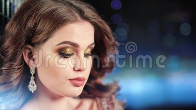 Close-up face of charming female model wearing jewelry shiny earrings at neon beams background. Portrait of beautiful woman with evening make-up and elegant stock footage