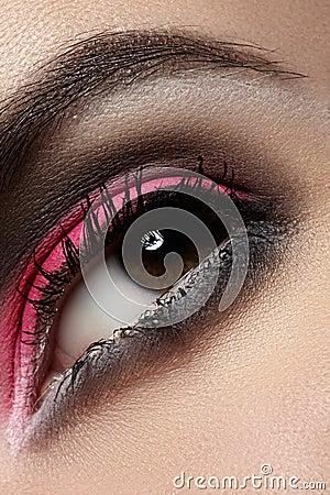 Close-up of fashion eyes make-up, bright magenta eyeshadow, dark eyebrows