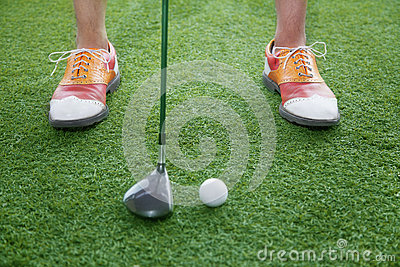 Close up on feet and golf club getting ready to hit a golf ball