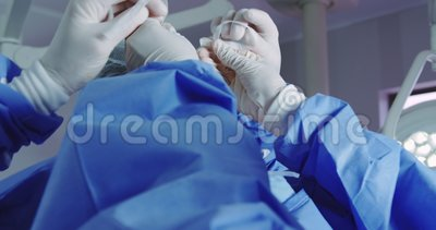 Close-up of female doctor helping male doctor to wear surgical mask in operation theater. They are getting ready for operation stock video