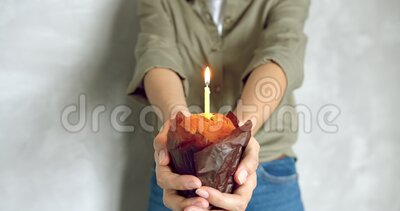 Close up of female hands holding a chocolate cake with a candle on a gray background. Birthday or anniversary concept.  stock video