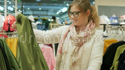 Close-up of female shopper, Choice of fashion clothes of different colors on hangers, Young attractive natural Blonde. Girl Makes purchases blouse in boutique stock footage