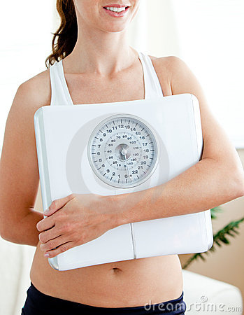 Close-up of a fit hispanic woman holding a scale