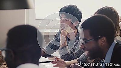 Close-up gelukkige Japanse jonge werknemer die en samen met collega's op multi-etnische bureauvergadering luisteren lachen stock video