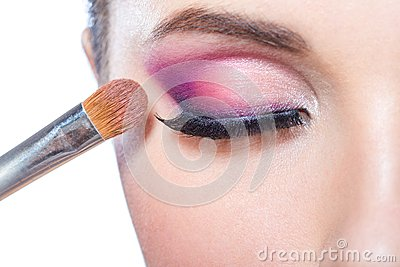 Close up of girl applying bright makeup