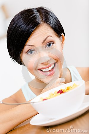 Close up of girl near the plate with cereals