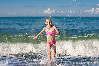 Close-up girl running from sea wave or surf