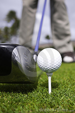 Close up of golf ball on tee and driver set up