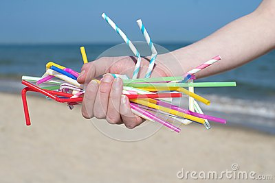 Close Up Of Hand Holding Plastic Straws Polluting Beach Stock Photo