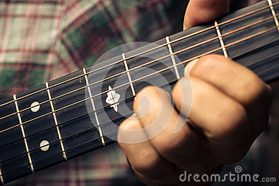 Close up on hand playing guitar