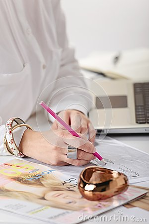 Close up of a hand s woman doing fashion sketches.