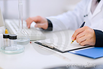 Close-up on hands of doctor working at table