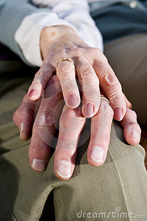 Close-up hands of senior couple resting on knee