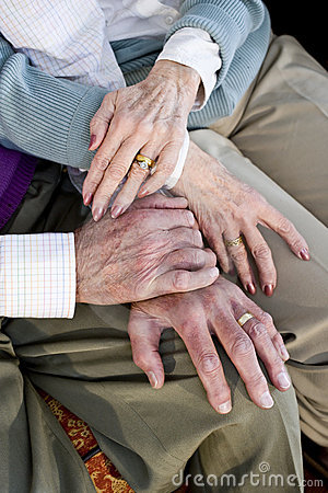 Close-up hands of senior couple resting on knees