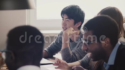 Close-up happy Japanese young employee listening and laughing together with colleagues at multiethnic office meeting. Successful millennial professional worker stock video