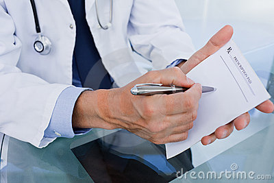 Close up of a male doctor showing a blank prescription sheet