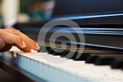 Close up of male hands playing piano.