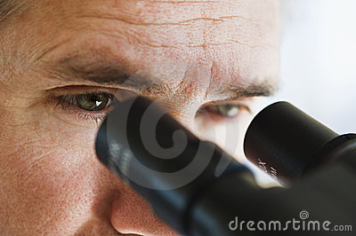 Close up of man s eyes looking through microscope
