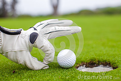 Close-up of a man s hand putting golf ball in hole
