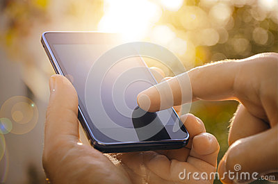 Close up of a man using mobile smart phone outdoor