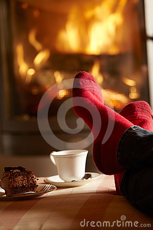 Close Up Of Mans Feet Relaxing By Cosy Log Fire