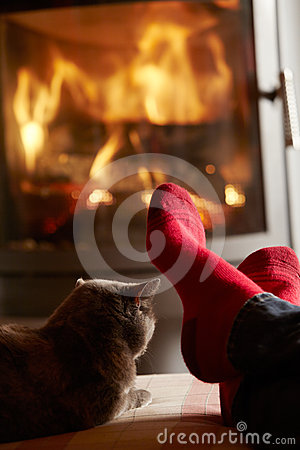 Close Up Of Mans Feet Relaxing by Fire With Cat