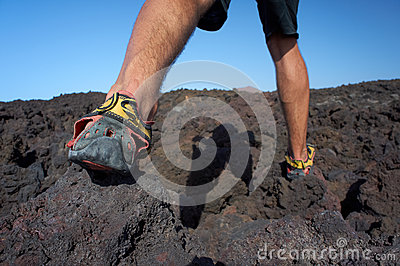 Close-up of mans feet walking on lava field