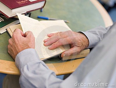 Close-up of mature student s hands turning book