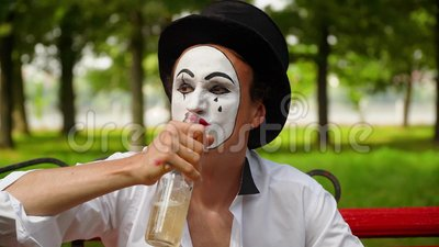 Close-up of a mime drinks alcohol outdoors. Bad habits. Mime in a black hat drinks alcohol outdoors. Bad habits stock video footage