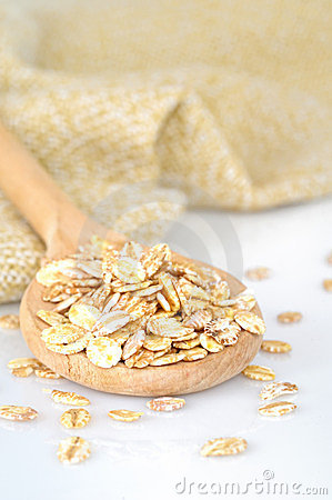 Close up of oat flakes in wooden spoon