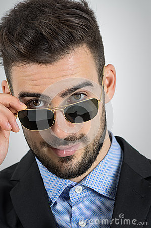 Free Close Up Of Young Flirting Man Looking Over Sunglasses. Stock Photos - 65164283