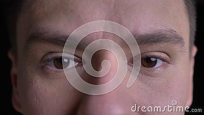 Close-up oog-portret van Kaukasische mens letten het op middelbare leeftijd ernstig op in camera op zwarte achtergrond stock video